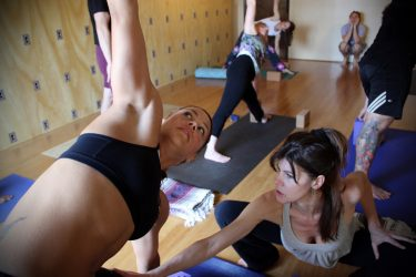 yoga teacher adjusting student