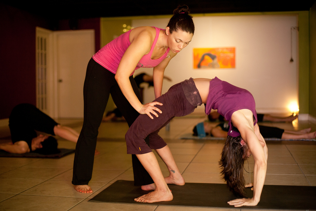 yoga teacher giving student assist