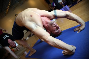 man practicing yoga pose wheel