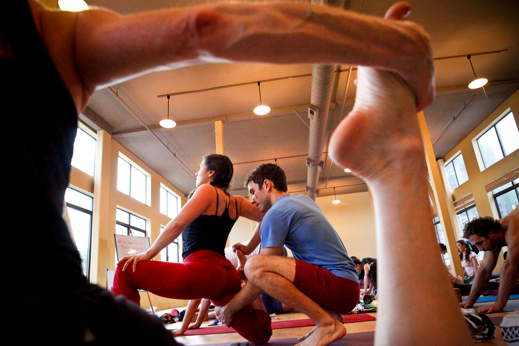 teacher assisting yoga student