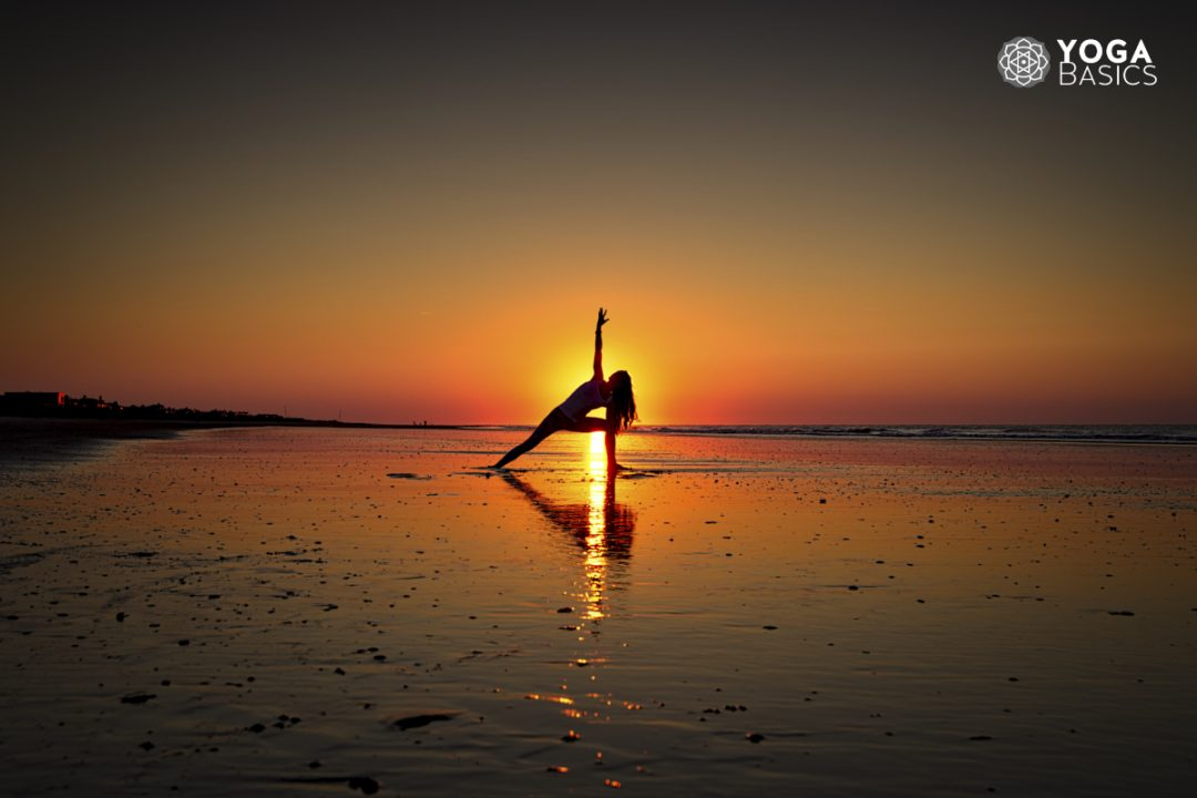 young woman practicing yoga on beach