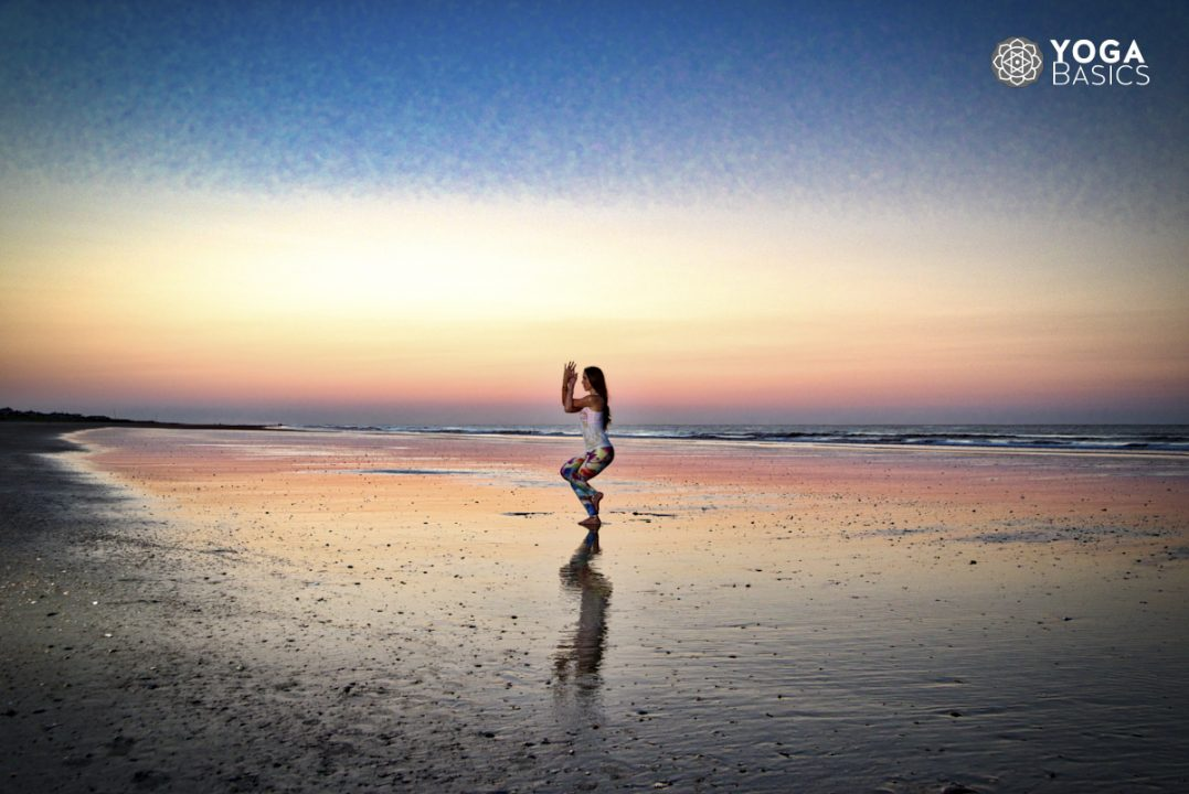 woman practicing eagle pose on beach